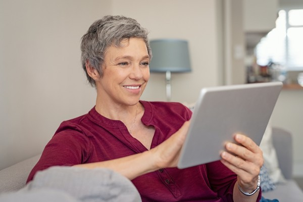 Woman leaving an assisted living review using her tablet.