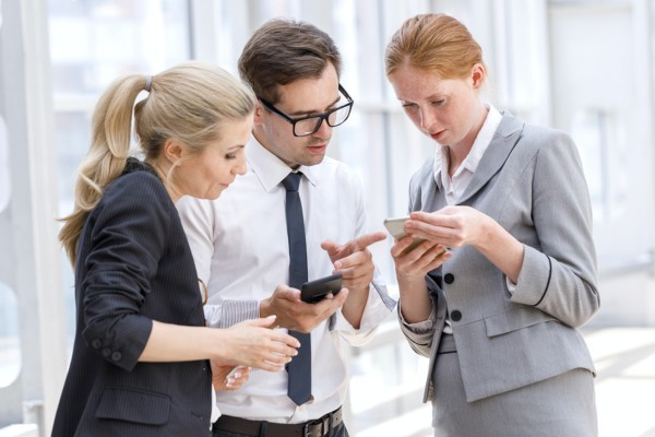 Three colleagues looking at information on a phone.