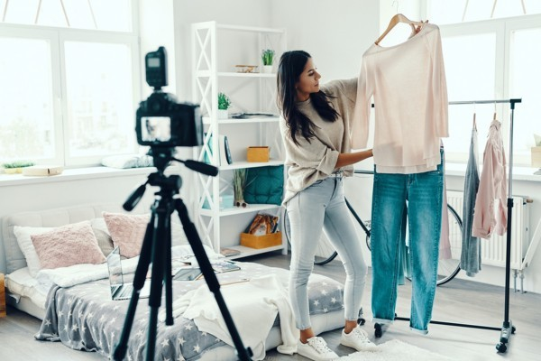 Woman taking photos of clothing for a shop.