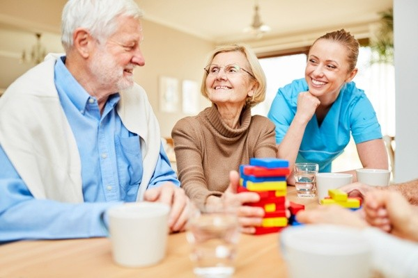 Smiling senior couple with an occupational therapist.